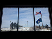 View out the window in the stairwell towards the football field and the American and Montana state flag at Bigfork High School