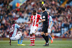 Referee Mark Clattenburg shows a yellow card to Stoke Midfielder Wilson Palacios (HON) as he helps up Aston Villa Forward Christian Benteke (BEL) who he fouled - Photo mandatory by-line: Rogan Thomson/JMP - 07966 386802 - 23/03/2014 - SPORT - FOOTBALL - Villa Park, Birmingham - Aston Villa v Stoke City - Barclays Premier League.