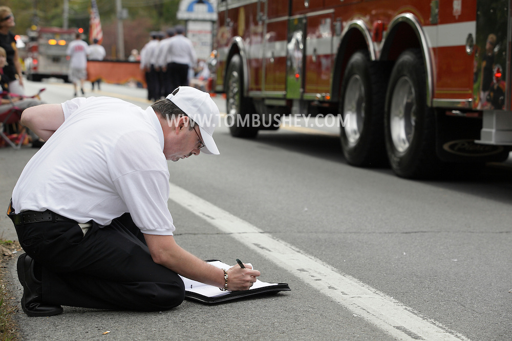 Salisbury Mills, New York - A judge makes notes as fire departments fire engines head down Route 94 during the Orange County Volunteer Firemen's Association (OCVFA) annual parade on Sept. 24, 2011.