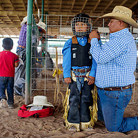Briceson James, right, helps his son Cole James strap on a helmet before competing in the wooly riding contest at the Navajo Nation Fair in Window Rock Friday.