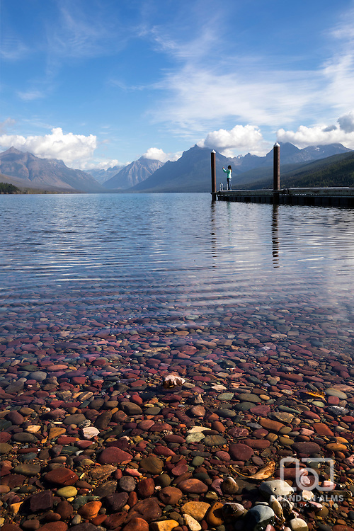 Young woman takes photos at the end of the pier at Lake McDonald in Glacier National Park, Montana.