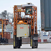Nederland Zuid-Holland Rotterdam  27-08-2009 20090827 Foto: David Rozing .Serie over logistieke sector.ECT Delta terminal in de haven van Rotterdam. Telescopische spreader voertuigen vervoeren de containers op de terminal naar de vrachtwagens voor verder transport. .ECT,European Container Terminals, at the Port of Rotterdam. Europe's biggest and most advanced container terminal operator, handling close to three- quarters of all containers passing through the Port of Rotterdam. ECT is a member of the Hutchison Port Holdings group (HPH), the world biggest container stevedore with terminals on every Continent. At the ECT Delta Terminal telescopic spreader vehicles transport the containers between ship and stack / trucks.  Terminal operations are highly automated for discharging and loading large volumes...Holland, The Netherlands, dutch, Pays Bas, Europe .Foto: David Rozing