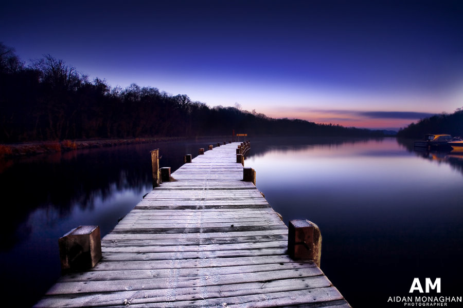 Twilight Jetty<br /> County Fermanagh<br /> by Aidan Monaghan<br /> A timber jetty, bristling with frost in the twilight of a winter&rsquo;s evening at Castle Archdale, County Fermanagh. The Photograph was taken at the turn of the new year in early January during an exceptionally cold spell of weather. It was the first time in years that I had observed such a substantial area of Upper Lough Erne completely frozen over for  an extended period of time. The deep freeze lasted almost two weeks. <br /> <br /> These beautiful but treacherous conditions produce some of the most stunning and seductive changes in colour and light that I have had the privilege to observe. In this photograph the sun has long since set yet the clear crisp winter sky is filled with the deep blues and magentas that you only get at this time of year. These colours our reflected by the Lough and absorbed by the individual ice crystals that have formed upon the jetty, giving it a subtle purple glow in the twilight.