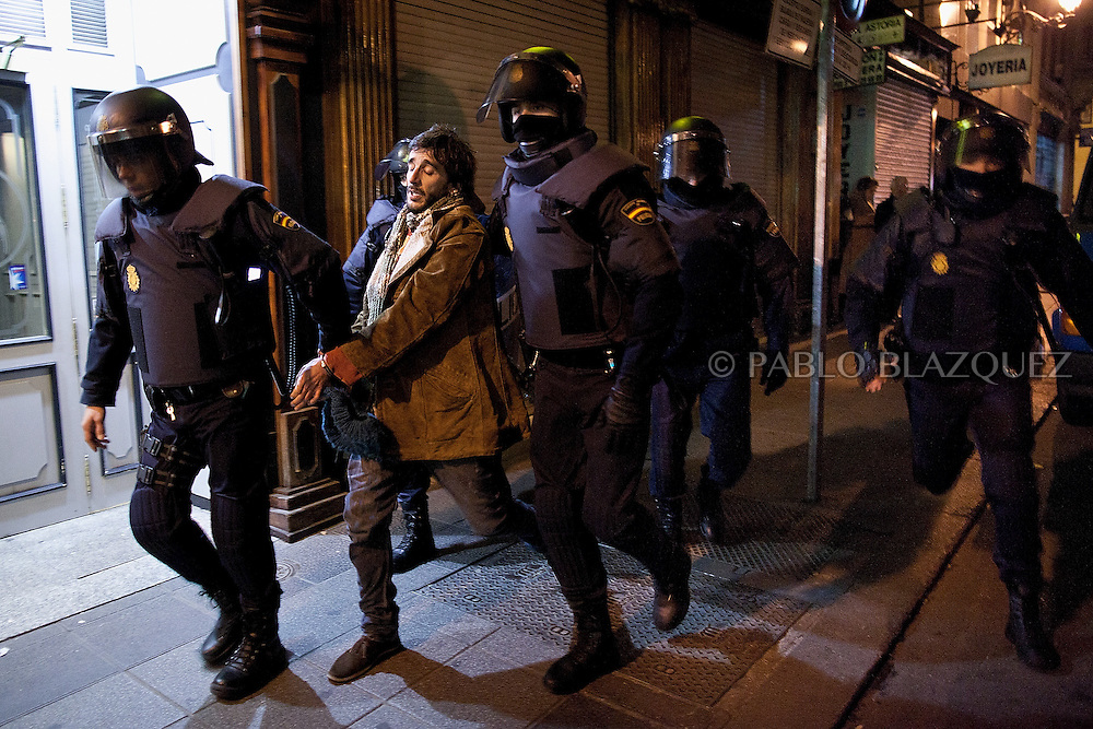 Policemen arrest a protester during clashes following a demonstration organized by Spain's 'indignant' protesters at the Puerta del Sol square in Madrid on February 10, 2012, hours after Spain's right-leaning government unveiled a labour reform. The number of jobless people in Spain shot above five million at the end of 2011, sending the unemployment rate to 22.85 percent -- double the European average and the highest in the industrialized world. Placard reads 'Against the labour reform.'