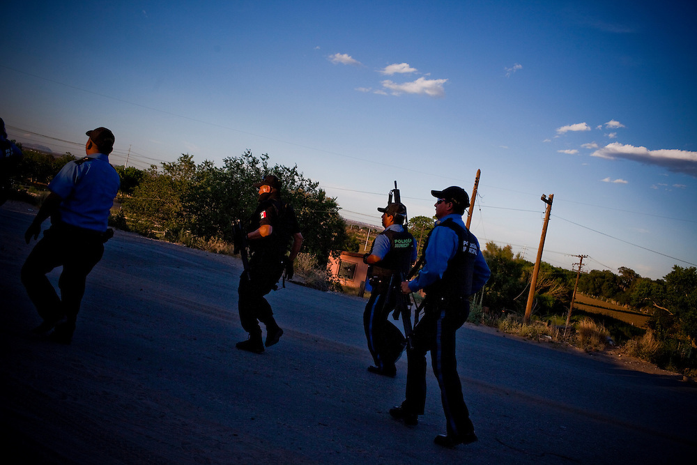 Ciudad Juarez Municipal Police run to a call after working an execution in El Valle de Juarez in May.