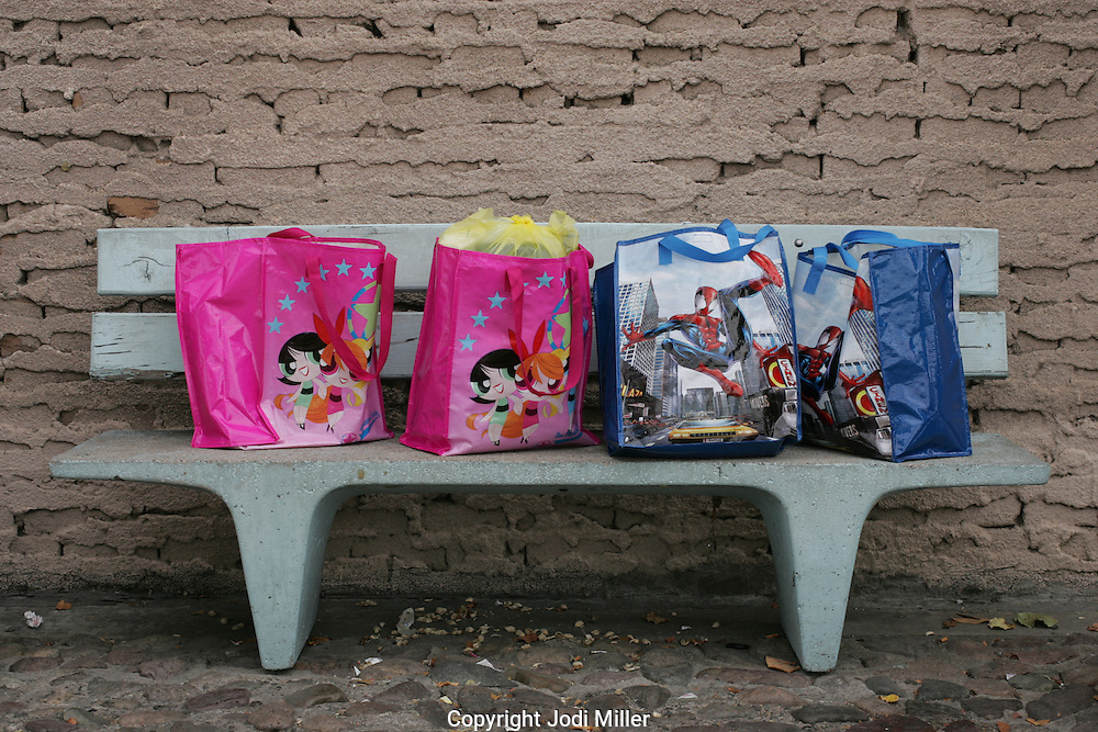 Boys and girls shopping bags sit on a bench in the boarder town of Nogales, AZ.