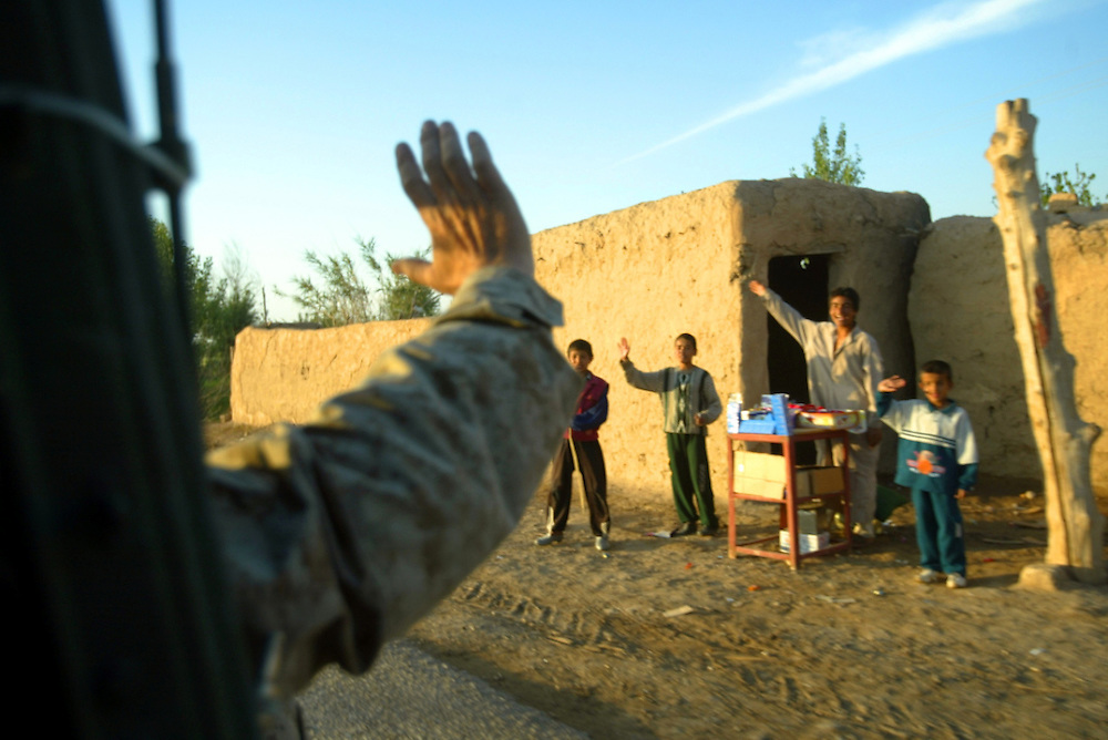 A US Marine waves out his Humvee window to some children as they drive through an area to maintain a presence in the Village near Tikret.