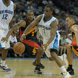 05 October 2008:  New Orleans Hornets guard Chris Paul (3) drives between Golden State Warriors defenders C.J. Watson (L) and Andris Biedrins (R)during a NBA preseason game between the Golden State Warriors and the New Orleans Hornets at at the New Orleans Arena in New Orleans, LA..