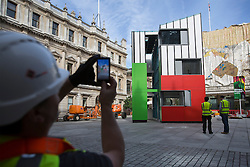 © licensed to London News Pictures. London, UK 13/08/2013. A worker taking pictures of a three and a half storey building called Homeshell which has been erected in the Courtyard in front of Burlington House in central London as part of the Royal Academy's current exhibition Richard Rogers RA: Inside Out. The Homeshell is a low-cost house that uses the pioneering technology with a flexible, quick and highly energy efficient building system which can be adapted to suit particularly highly urban or small sites. Photo credit: Tolga Akmen/LNP