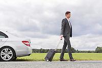 Full length side view of young businessman with suitcase leaving broken down car at countryside