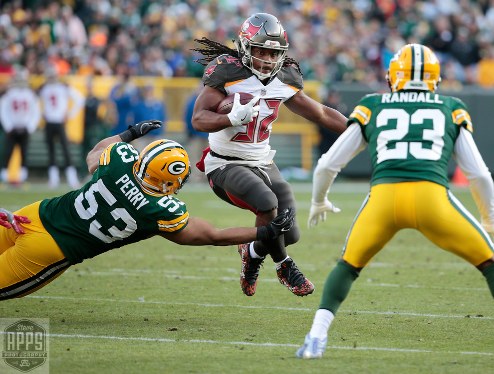 Tampa Bay Buccaneers running back Jacquizz Rodgers (32) on a 3-yard run in the 3rd quarter. Rodgers is tackled by Green Bay Packers outside linebacker Nick Perry (53).<br /> The Green Bay Packers hosted the Tampa Bay Buccaneers at Lambeau Field in Green Bay,  Sunday, Dec. 3, 2017. The Packers won in 26-20 in Overtime.   STEVE APPS FOR THE STATE JOURNAL.