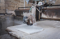 SIRACUSA, ITALY - 8 NOVEMBER 2016: The marble that will be used for the gravestone of Musaab Shabani, a victim of the August 24th 2014 shipwreck, is cut here at the Gibilisco marble-worker's workshop in Siracusa, Italy, on November 8th 2016.<br /> <br /> Musaab Shabani was buried in the cemetery of Sortino, marked by a gravestone with the number nine because at the time he hadn't been identified yet. He was later identified by his brother Abd thanks to the efforts of policeman Angelo Milazzo. Since then, Abd has arranged to have a gravestone made bearing his brother's name and date and place of birth as well as a religious inscription in Arabic, bringing a final bit of closure to this tragic chapter. <br /> <br /> On August 24th 2014, a boat carrying more than 400 migrants, departed from the coasts of Libya in the attempt to reach Italy, capsized in international waters in the Mediterranean Sea. Rescuers of the Italian Navy saved 352 people, and recovered 24 lifeless bodies.<br /> <br /> Following the events of the Arab Spring in 2011, including Gaddafi's death and Libya's plunge towards chaos, clandestine crossings skyrocketed, as did the number of people drowning. In 2014 over 170,000 arrived in Italy and since then more than 10,000 perished in the Mediterranean sea.<br /> <br /> Only a fraction of these bodies have ever been recovered, and, of the ones that have, the majority remain unidentified. In Sicily alone there are more than 1,500 graves of anonymous refugees and migrants–people from Syria and other war torn countries–who have drowned in shipwrecks at sea.<br /> <br /> Despite the decades long persistence of the problem, Italy has yet to develop a comprehensive approach to handling the bodies of shipwreck victims. Many pieces of a functional body identification system are in place, but its overall effectiveness is crippled by a lack of coordination between the various local agencies involved and national authorities.