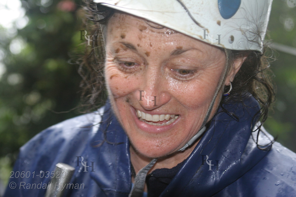 Ecoteach participant L'Ann Seibel smiles with rust-spattered face during rainy zipline adventure through the Monteverde cloud forest on Sky Trek cables; Monteverde, Costa Rica.