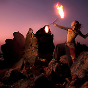 A Japanese juggler performs with fire sticks on the rocks at Arambol beach in north Goa.