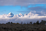 Grand Teton Mountains covered with fresh snow, clouds and blue sky