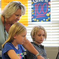 Myrtle Attendance Center fourth grade math teacher Kristi Cox helps one of her students Lilly Kate Scott, 11, with some classwork Thursday morning.
