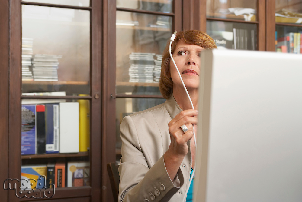 Woman holding and inspecting computer cable in living room