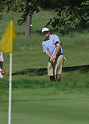 Defending Michigan Amateur Champion Christian Vozza of Traverse City watches his chip shot on the 9th hole of the Heather course at Boyne Highlands.