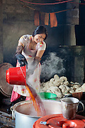 A Nepali woman pours hot dye for cotton into a large container at the Womens Skills Development Project in Pokhara, Nepal. The WSDP was set up in 1975 as a non-profit, fair trade organization to help disadvantaged women in Nepal.
