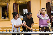 "14 MARCH 2006 - PHNOM PENH, CAMBODIA: People pray and make offerings at a small pagoda in front of the Royal Palace in Phnom Penh, Cambodia to pray. The pagoda serves as the ""spirit house"" of the palace. The Cambodians (and Thais) build small spirit houses, which have great religious significance, in front of the homes and usually businesses. They pray at the spirit homes and frequently leave small offerings of fruit and small change in them. The spirit house for the Palace has become a public shrine and there are usually people there praying, leaving donations and lighting incense. PHOTO BY JACK KURTZ"