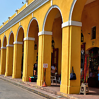 Las Bóvedas in Old Town, Cartagena, Colombia<br /> What today appears as a shopping arcade was designed as bombproof vaults when they were built near the Caribbean shoreline in 1798. They were originally used by the Spanish to house ammunition.  Later, the 49 foot walls were converted into 23 prison cells.  Now you will find boutique stores selling local crafts and souvenirs behind the 47, brightly colored arches of Las Bóvedas in the San Diego area of Old Town.