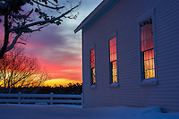 A colorful sunrise is reflected in the three windows of the old white church on Orr's Island.<br /> <br /> Harpswell, Maine