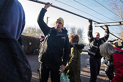 Harefield, UK. 18 January, 2020. Blind Paralympian James Brown (l) assists activists from Extinction Rebellion, Stop HS2 and Save the Colne Valley in passing through fencing placed by enforcement agents acting for HS2 across a public footpath leading to Stop HS2's Colne Valley wildlife protection camp. They are attending a three-day 'Stand for the Trees' event timed to coincide with tree felling work by HS2. The enforcement agents have been evicting Stop HS2 activists from the camp for the past week and a half. 108 ancient woodlands are set to be destroyed by the high-speed rail link.