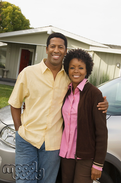 Couple Standing in Front of Minvan and Home