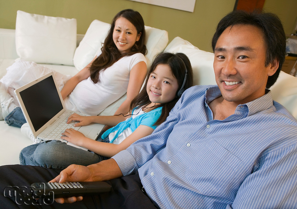 Family Relaxing in Living Room with Laptop
