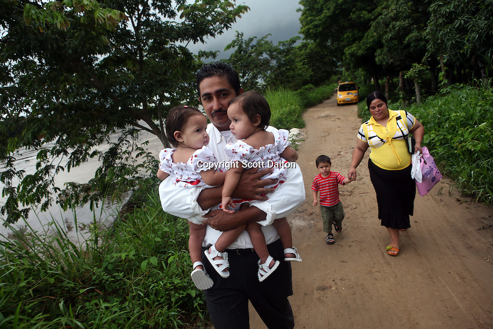 A man carries his children to a church service in Arauca, Colombia on the Colombian and Venezuelan border, on June 28, 2009. The border region between Colombia and Venezuela has often been a region with a high level of activity of illegal armed groups. (Photo/Scott Dalton)