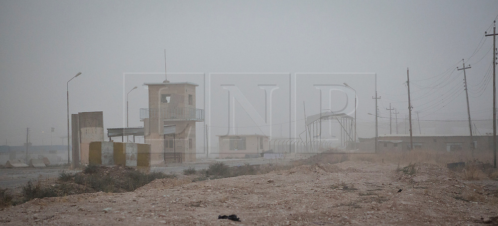 © Licensed to London News Pictures. 28/09/2014. Rabia, Iraq. A sandstorm moves in to hamper visibility at the Iraq-Syria border crossing towns of Al-Yarubiyah, Syria, and Rabia, Iraq.<br /> <br /> Facing each other across the Iraq-Syria border, the towns of Al-Yarubiyah, Syria, and Rabia, Iraq, were taken by Islamic State insurgents in August 2014. Since then The town of Al-Yarubiyah and parts of Rabia have been re-taken by fighters from the Syrian Kurdish YPG. At present the situation in the towns is static, but with large exchanges of sniper and heavy machine gun fire as well as mortars and rocket propelled grenades, recently occasional close quarter fighting has taken place as either side tests the defences of the other. Photo credit: Matt Cetti-Roberts/LNP