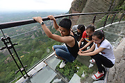 YUEYANG, CHINA - MAY 27: (CHINA OUT)<br /> <br /> Hitting the high notes! China unveils another terrifying glass walkway... and this one is also a giant KEYBOARD that plays musical notes as you walk<br /> <br /> Terrifying 'skywalks' have become a popular activity for Chinese tourists seeking a thrill.<br /> But now local authorities in Hunan province have built the country's first glass walkway that plays music as you walk, in an attempt to soothe the fears of visitors.<br /> The path, which is built along the edge of a cliff nearly 1,000 feet above ground, doubles up as a giant keyboard by responding to footsteps,<br /> Tourists have already been pictured walking tentatively down the 180-metre long glass bottomed path, which is sure to get stomachs churning.<br /> However, those brave enough to get up there are treated to panoramic views of the whole of Pingjiang County, designated an area of outstanding natural beauty.<br /> The walkway consists of two layers of 12mm thick glass glued together and electronic components can respond to footsteps with 70 different notes.<br /> The interactive path in the Shiniuzhai National Park is the first of its kind, although glass walkways appear to be cropping up all across the country recently.<br /> Last month the construction of a walkway in the same scenic spot received widespread attention online after workers were picture walking precariously along wooden planks at the edge of a cliff thousands of feet in the air.<br /> Pingjiang is already very popular with tourist for its Mufu Mountain range and the national park attracts thousands of visitors every year. <br /> Local authorities have been trying to attract even more tourists by building a series of winding mountain paths and glass walkways in the region.<br /> ©Exclusivepix Media