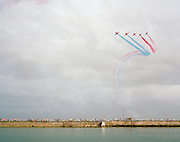 Hawk aircraft of the 'Red Arrows', Britain's Royal Air Force aerobatic team display above Guensey harbour crowds.