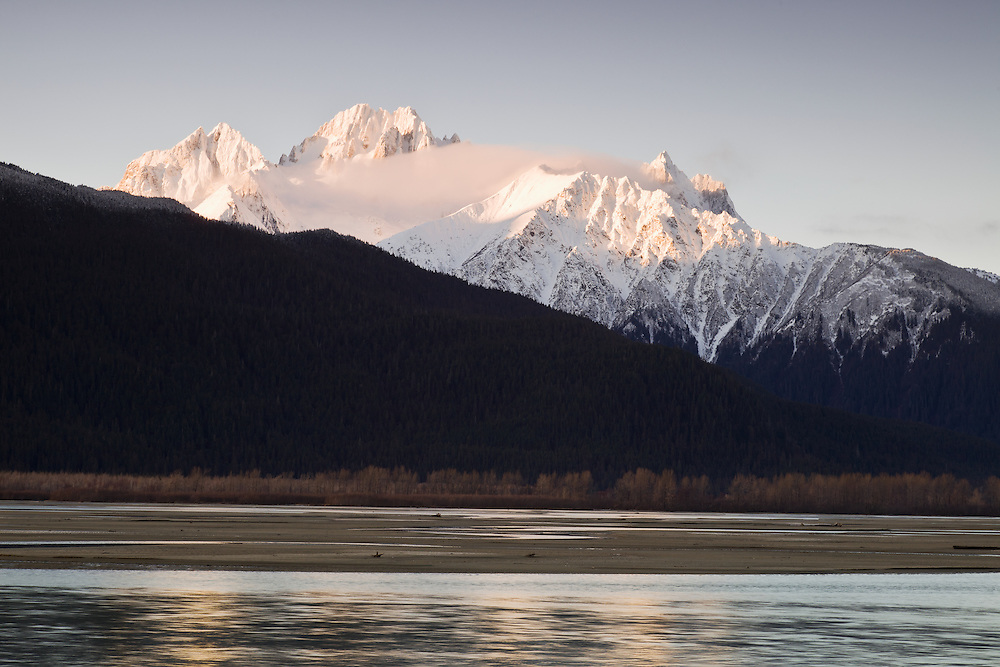 Sunrise creates alpenglow on the Chilkat Mountains and Chilkat River near the Chilkat Bald Eagle Preserve near Haines in Southeast Alaska. Morning. Winter.