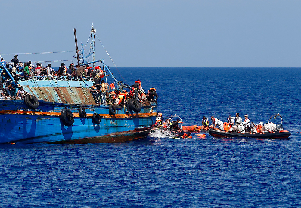Migrants in the water scramble to get onto Migrant Offshore Aid Station (MOAS) rescue boats launched from the MOAS ship Phoenix after they  jumped from an overloaded wooden boat during a rescue operation 10.5 miles (16 kilometres) off the coast of Libya August 6, 2015.  An estimated 600 migrants on the boat were rescued by the international non-governmental organisations Medecins san Frontiere (MSF) and MOAS without loss of life on Thursday afternoon, a day after more than 200 migrants are feared to have drowned in the latest Mediterranean boat tragedy after rescuers saved over 370 people from a capsized boat thought to be carrying 600.  Picture taken August 6, 2015.<br /> REUTERS/Darrin Zammit Lupi <br /> MALTA OUT. NO COMMERCIAL OR EDITORIAL SALES IN MALTA