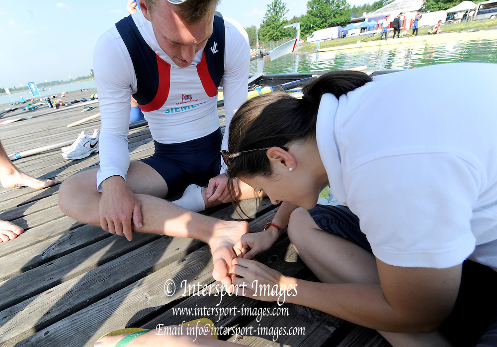 Munich, GERMANY,  General views, GV' s Boating area. GBR M4- Stroke Alex GREGORY, picks up a wooden splinter while preparing to boat. FISA world Cup Rd 1. Munich Olympic Rowing Course,  Thursday  26/05/2011  [Mandatory Credit Peter Spurrier/ Intersport Images]
