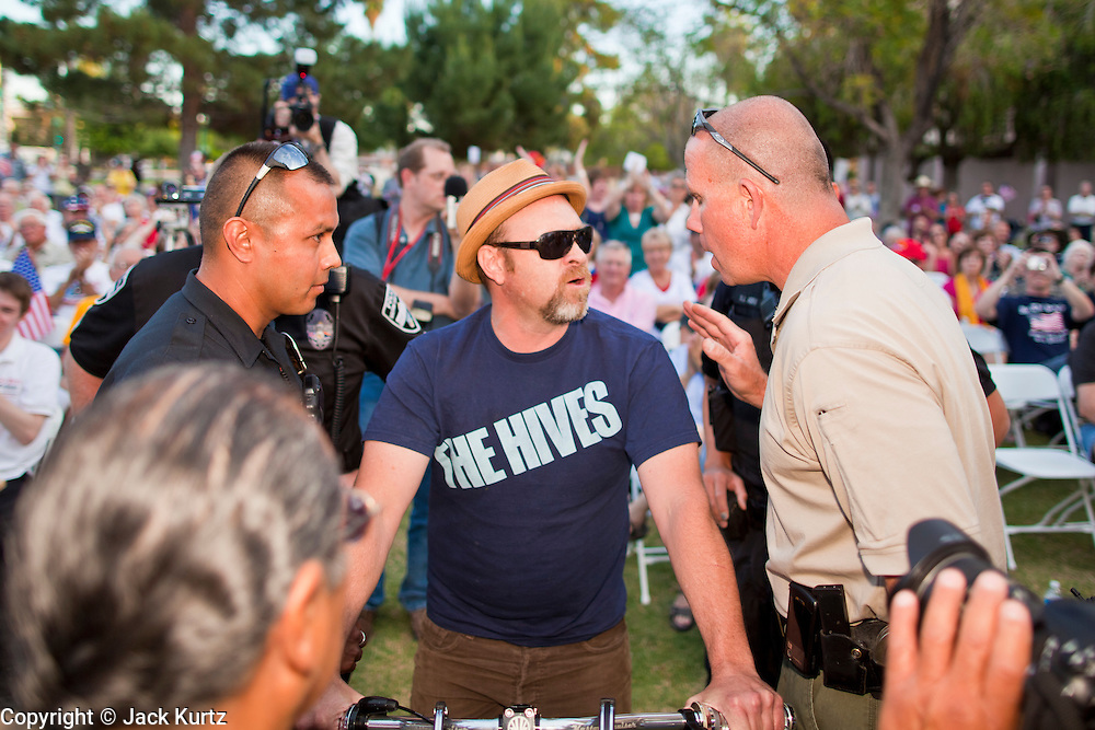 15 APRIL 2011 - PHOENIX, AZ: Police talk to a man who sat on his bike in the front row of the Tea Party rally in Phoenix Friday. The man was ultimately arrested. About 500 supporters of the Tea Party movement rallied Friday at the Arizona State Capitol to mark tax day. They protested high taxes, the federal deficit, the debt limit and immigration policy. About 50 pro-immigrant protesters held a counter rally at the capitol. At least one person was arrested, and others led away by police after several shouting matches between Tea Party supporters and the immigrants rights protesters broke out.     Photo by Jack Kurtz