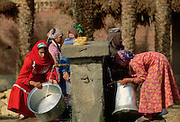 December 1993, Egypt --- Women fill large metal containers with water from a communal well. --- Image by © Owen Franken/CORBIS