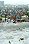 A hand of an abseiler, working on the facade of a block of flats in Chelsea, London, UK.