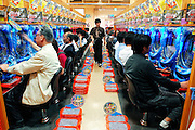"Customers play ""pachinko,"" a game sometimes referred to as Japanese pinball, at a pachinko parlor in Tokyo, Japan. Pachinko is a game unique to Japan, in which players first purchase small metal balls that are then inserted into the machine with the purpose of attempting to win more balls. Accumulated balls can be exchanged for prizes such as vouchers, tokens (usually small pieces of gold in plastic cases) or a range of goods. There is also a method of exchanging the winnings for cash, though this is illegal. Despite the fact that gambling is officially illegal in Japan, there are some 13,000 pachinko halls, known as ""pachinko parlors"", scattered throughout the country, mostly located near to main line railway stations, but some are found in the middle of the countryside, their neon signs lighting up the paddy fields near which they stand. Some of the larger ones host several hundred playing machines. There are also hundreds of pachinko magazines guiding readers the key to winning the game, and there are even those people who make a living from the game. Known as ""pachi-puro,"" or professional pachinko players, the best of these players can earn around 600,000 yen (US$6,000) per month from the game.  .."
