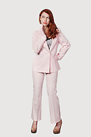 Beautiful young businesswoman in pink suit standing against gray background