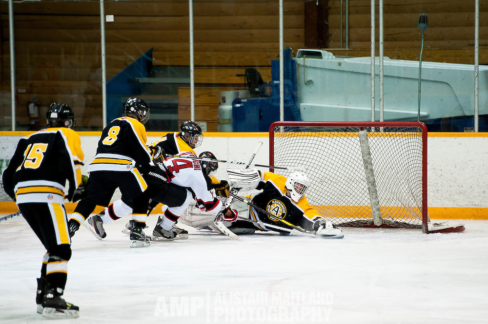 Jamie Tetlichi of the Whitehorse Mustangs is stopped just short of of a goal by Aldengrove goalie Cole Andersen.