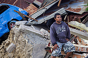 Portrait of Ronald (32) in front of his Father's (Sabudin) car repair shop who was killed  when he a sinkhole swallowed the Balaroa Village after a 7.5 earthquake magnitude hit off the coast of Donggala, Palu Sulawesi Central, Indonesia on Sept. 28th causing a tsunami.  Ronald was able to save 6 other family members including his mother, 2 sister in law, 1 younger sister, 1 older brother and 2 nephews. <br /> <br /> Sabudin owns a car repair shop for many decades<br /> <br /> <br /> Residents fear as much as 70 per cent of the population there has been killed. The rural village — a few kilometres outside Palu — was home to about 2,000 people until Friday.  Search and rescue workers using earth-moving equipment have toiled for days to find survivors.  But more than 1,000 people are still missing,