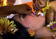 "TOOTH FILING IN BALI<br /> <br />  5am in a little village of south Bali, Indonesia. For two days the teens have prayed in a special place and are now ready for the tooth filing ceremony. The whole village combined the ceremony to reduce the high costs.<br />  The girls and even the boys have a make up session. The young people are dressed in gorgeous clothing and big headdresses that are rented for the celebration. The atmosphere looks more like a movie set than a religious celebration.  Balinese tooth-filing is an ancient tradition that predates Hinduism's arrival on the island in the 5th century BCE. Ancient tradition meets now the modern techniques with metal braces that have invaded Asia for years now.  The teeth of gods and spirits are always pointed and long. They are likened to those of ferocious evils, wild animals, or dogs. It's believed a Balinese may be denied entrance into heaven if the teeth are not filed because she might be mistaken for a wild creature.  The tooth filing ceremony starts in the temple with the mebyakala , a series of purification with holy water made by the big priest (pedanda' ) ceremony to ""cleanse"" the teenagers before having their teeth filed   The aim of the ceremony is to symbolically ""cut down"" on the six negative traits that are inherent in humans (like the 7 sins in Christianity) : lust, greed, wrath, pride, jealousy, and intoxication.  Tooth filing is a rite of passage into adulthood. The teens bow in front their parents and thanks them for everything they've since they were born. It is a very sequence full of emotions.  The teens show respect to her parents in front of the whole family and many end in tears. The teens have to go thru the ceremony when a boy's voice change or when the girls has her first menstruations.  Before the filing begins, the priest says superstitious sentences. A ruby ring that is believed to have huge power is used to protect the teen from the evil. The stone touches the teeth as the protection symbol"