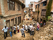 04 AUGUST 2015 - KHOKANA, NEPAL: Workers remove earthquake debris from the streets in Khokana, a village about an hour from Kathmandu. Three months after the earthquake, roads in many rural villages are still blocked by earthquake debris. The Nepal Earthquake on April 25, 2015, (also known as the Gorkha earthquake) killed more than 9,000 people and injured more than 23,000. It had a magnitude of 7.8. The epicenter was east of the district of Lamjung, and its hypocenter was at a depth of approximately 15km (9.3mi). It was the worst natural disaster to strike Nepal since the 1934 Nepal–Bihar earthquake. The earthquake triggered an avalanche on Mount Everest, killing at least 19. The earthquake also set off an avalanche in the Langtang valley, where 250 people were reported missing. Hundreds of thousands of people were made homeless with entire villages flattened across many districts of the country. Centuries-old buildings were destroyed at UNESCO World Heritage sites in the Kathmandu Valley, including some at the Kathmandu Durbar Square, the Patan Durbar Squar, the Bhaktapur Durbar Square, the Changu Narayan Temple and the Swayambhunath Stupa. Geophysicists and other experts had warned for decades that Nepal was vulnerable to a deadly earthquake, particularly because of its geology, urbanization, and architecture.     PHOTO BY JACK KURTZ