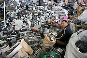 A worker is dwarfed by a pile of electronic trash in a Guiyu workshop, where workers take apart electronics for recycling and incineration.