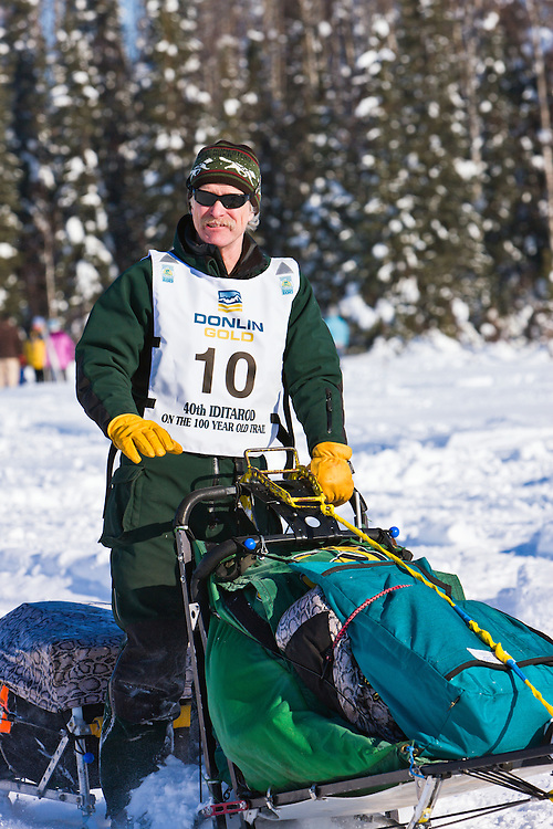 Musher Jeff King competing in the 40th Iditarod Trail Sled Dog Race on Long Lake after leaving the Willow Lake area at the restart in Southcentral Alaska. Afternoon. Winter.