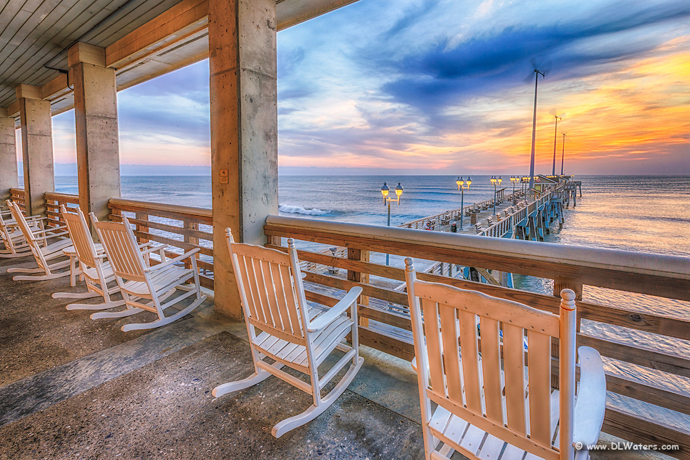 A line of rocking chairs looking out over Jennette's Pier in Nags Head, NC.