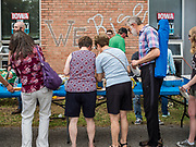 27 MAY 2019 - URBANDALE, IOWA: People line up for food at a Memorial Day barbecue hosted by US Senator Cory Booker (D-NJ) at his Iowa campaign office. Sen. Booker is running to be the Democratic nominee for the US Presidency. Iowa traditionally hosts the the first selection event of the presidential election cycle. The Iowa Caucuses will be on Feb. 3, 2020.                  PHOTO BY JACK KURTZ