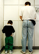Man and boy sat urinals in a public toilet Cardiff Wales 1990's